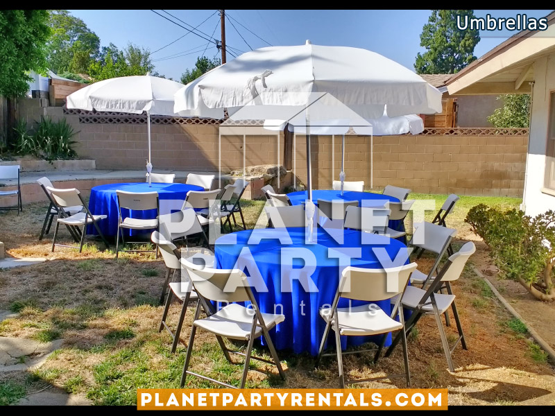 White Umbrella with Royal Blue Tablecloth and Plastic Chairs