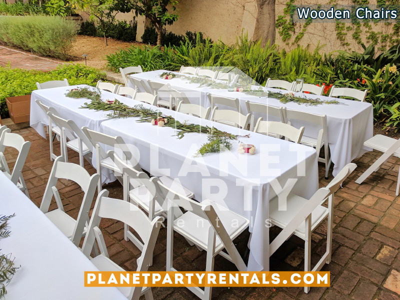 White Wooden Chairs with White Rectangular Tablecloths and Flower Decorations for Wedding Event