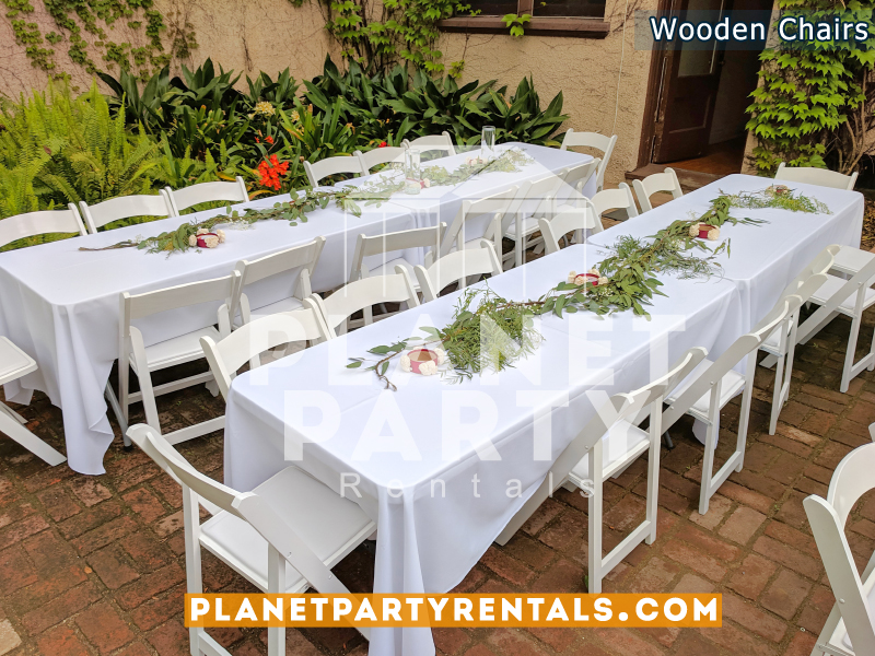 White Wooden Chairs with White Rectangular Tablecloths and Flower Decorations for Wedding Event White Wooden Chairs with White Rectangular Tablecloths and Flower Decorations for Wedding Event
