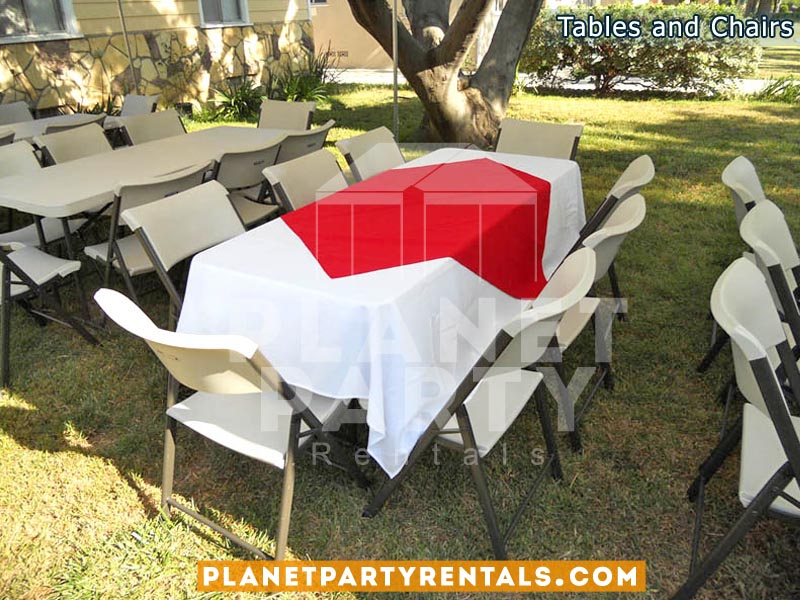 White plastic chairs with white table cloth and red diamond / overlay
