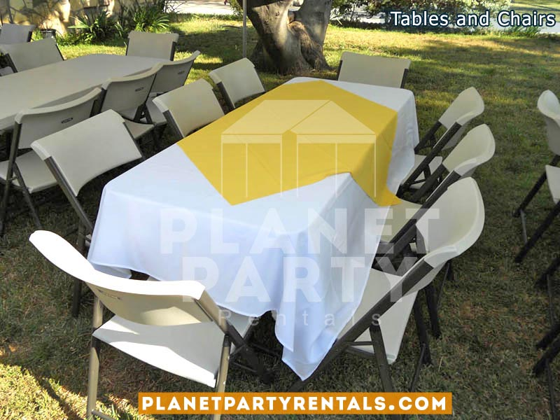 White plastic chairs with white table cloth and yellow diamond / overlay